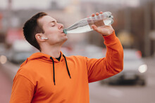 Athlete Man In Orange Hoodie Drinking Water From Bottle Outdoor
