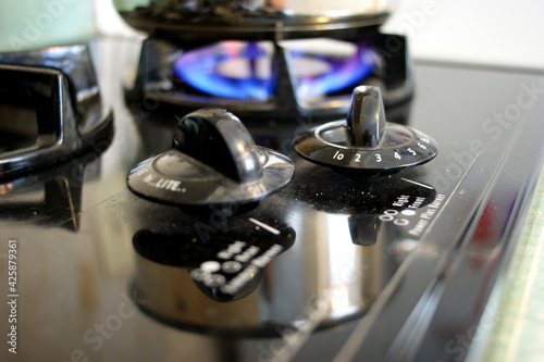 Pot cooking on gas stove with knobs in foreground #425879361