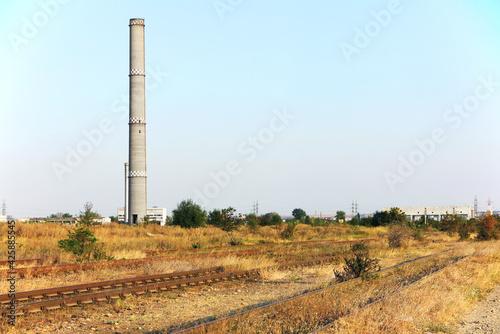 Fotografie, Obraz Abandoned chimney of an thermal power station, near the railways