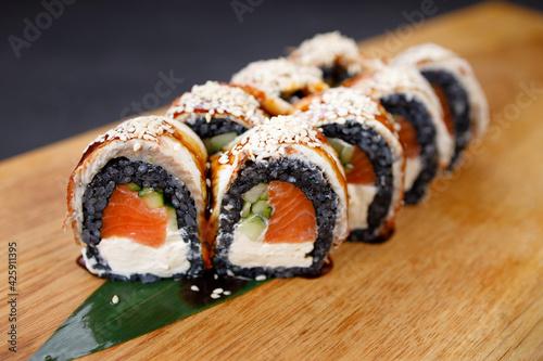 Fototapeta Seafood delicatessen salmon sushi black maki rolls obraz