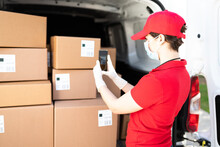 Caucasian Courier Checking The Shipping Labels With A Smartphone