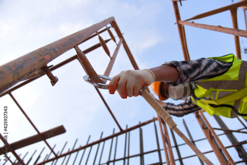 Fototapeta Construction workers hook up safety belts At construction working  buildingWorking at height equipment Construction worker wearing safety harness and safety line working on construction at high place.