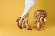 Female Feet Fashionable Shoes Elegant Style Head Sculpture Yellow Background