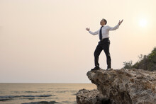 Asian Businessman Standing On The Cliff With Two Arms Rising Showing Of Great Pleasure Or Happy Satisfaction Of Enjoyment When Business Target Reached Or Hard Job Finished