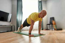 Athletic Mature Man Fitness Instructor In Sportswear Standing In A Plank On Yoga Mat While Exercising At Home In Living Room