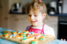 Cute Little Toddler Girl And Fresh Baked Homemade Easter Or Spring Cookies At Home Indoors. Adorable Blond Child With Apron With Bunny And Carrot Cookie In Domestic Kitchen. Child Eating Cookie