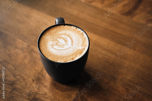 Cappuccino coffee with latte art on wooden table. Black cup and beautiful milk foam. Soft focus
