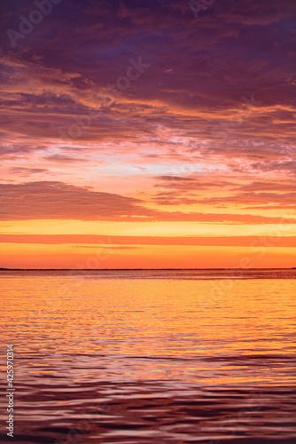 Dramatic sky. Sunrise sun over ocean water. Natural sunset.