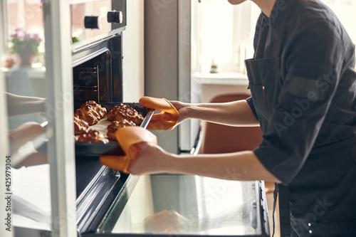 Canvas Print Professional confident woman is preparing custard cakes at light modern kitchen