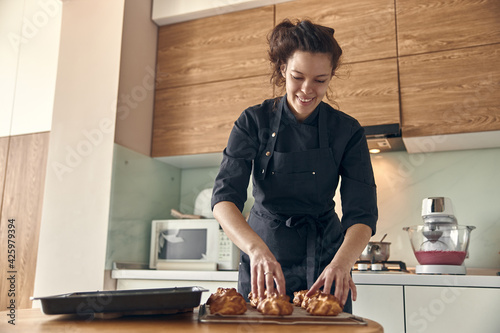 Obraz na płótnie Professional confident woman is preparing custard cakes at light modern kitchen