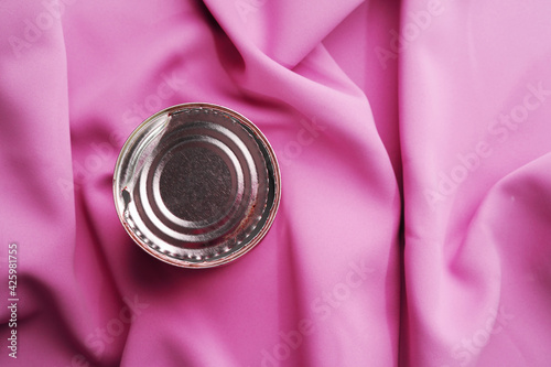 Tin can on pink silky fabric, aesthetic concept