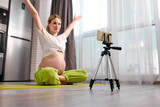 calm caucasian pregnant woman sit doing exercises on floor and recording video