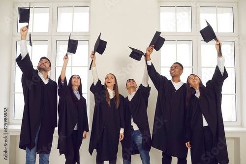 Obraz Persons are happy to be graduates. Group of multiracial graduate students lift up their academic hats standing in classroom. Concept of successful completion of an important educational stage in life. - fototapety do salonu