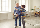 Happy excited grandpa celebrates Grandparents Day and enjoys sports games together with his grandson. Little boy and his grandfather playing soccer in the living-room, laughing and having fun