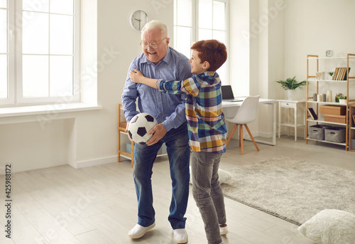 Obraz na plátně Happy excited grandpa celebrates Grandparents Day and enjoys sports games together with his grandson