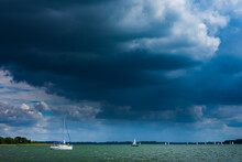 Sailing Yacht In The Lake With Gloomy Sky Before The Rain. Yacht Sailing On The Lake Against A Blue Sky With Clouds. Sailboat Vacations On A Lake.