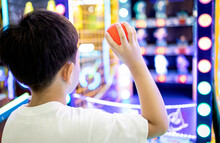 Kid Boy Playing A Game Of Darts,holding A Small Plastic Ball In His Hands,aiming Throwing At A Target Or A Toy Doll To Knock It Down,little Child Hurl The Ball At The Toys Placed On The Shelf To Fall