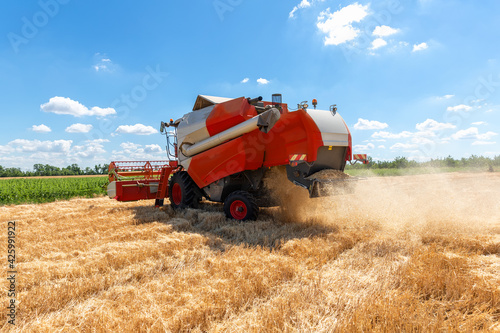Photo Scenic front view Big powerful industrial combine harvester machine reaping golden ripe wheat cereal field on bright summer or autumn day