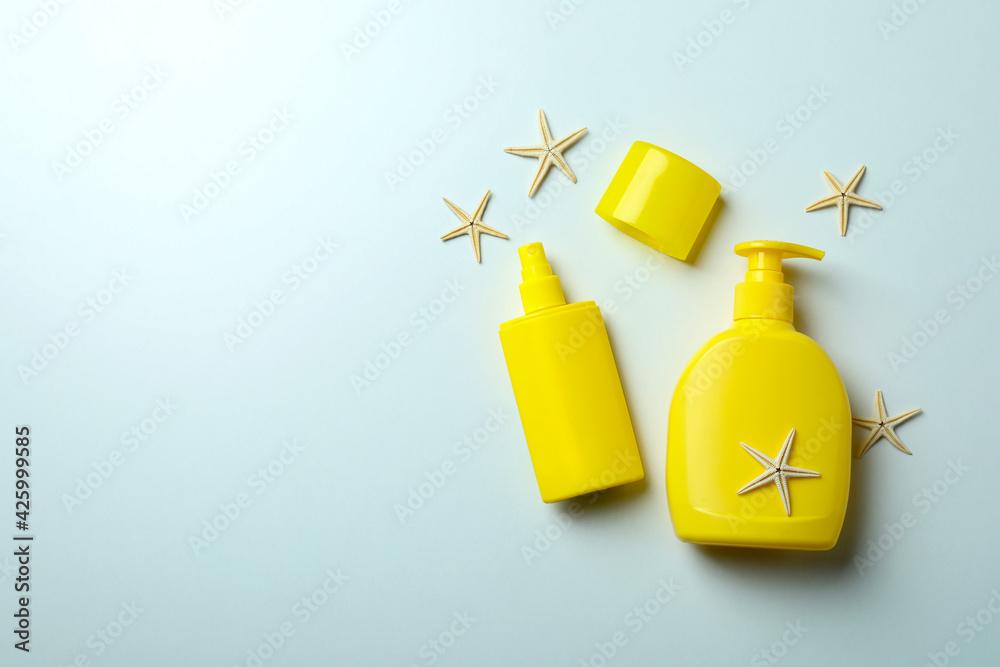 Fototapeta Bottles of sunscreen and starfishes on white background