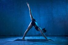 Sporty Attractive Woman Wearing Black Sportswear Standing In Yoga Asana With Raised Leg Under Rain. Strong Flexible Girl Standing In Downward Facing Dog, Adho Mukha Svanasana Pose.