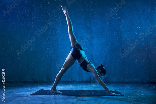 Fotografija Sporty attractive woman wearing black sportswear standing in yoga asana with raised leg under rain