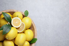 Many Fresh Ripe Lemons With Green Leaves On Light Grey Table, Top View. Space For Text