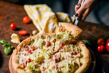 Side View Of A Slice Of Pizza On A Spatula And Pizza On A Wooden Board With Caesar Sauce, Iceberg Lettuce, Cherry Tomato Slices, Parmesan Cheese, Quail Eggs On A Brown Background