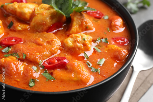 Bowl of delicious chicken curry on table, closeup