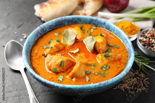 Bowl of delicious chicken curry on black table