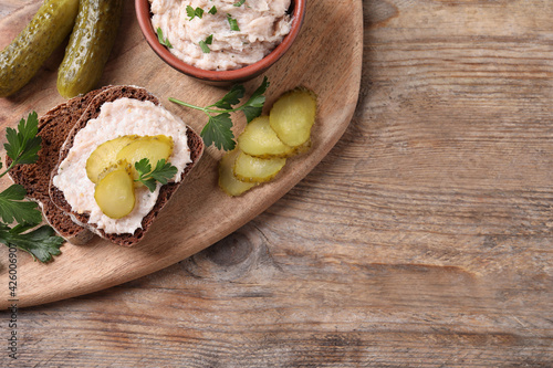 Sandwich with delicious lard spread and pickles on wooden table, flat lay. Space for text