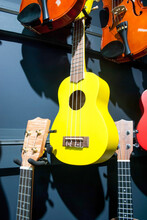 Yellow Ukulele And Violins Hanging On Wall Sale In Music Store