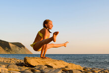 A Girl At Sunset By The Sea Stands In A Gymnastic Handstand. The Girl Practices Yoga On The Seashore.