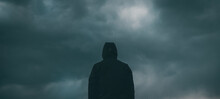 Rear View Of Male Person Wearing Hooded Jacket Against Dark Moody Dramatic Clouds At Sky