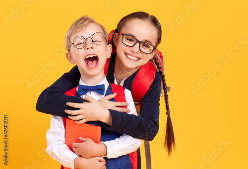Obraz na plátně Happy schoolgirl giving piggyback ride to boy
