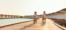 Carefree Mother And Daughter Riding Bicycles Along Wooden Promenade