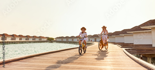 Canvas Print Carefree mother and daughter riding bicycles along wooden promenade