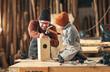 Leinwandbild Motiv Kid with dad assembling wooden bird house in craft workshop