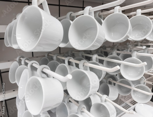 Papel de parede A group of white ceramic cups hung on a stand in the kitchen