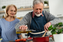 Senior Woman And Man Cooking In The Kitchen. Happy Husband And Wife Preparing Delicious Food At Home..