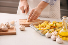 Woman Cutting Garlic On Table In Kitchen