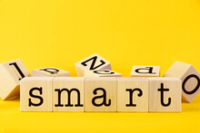 The Word SMART. Wooden Cubes With Letters On A Yellow Background. Conceptual Image.