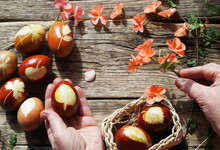 Easter Background. Eggs Are Laid Out In A Circle With Sprigs Of Plants And Pelargonium Flowers On A Wooden Vintage Background.Place For Your Text.