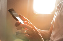 Woman's Hands Holding A Black Smart Phone With Blank Desktop Screen Next In The Cabin At The Window Airplane
