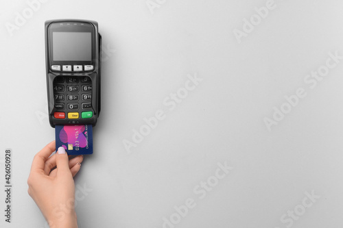 Fotografie, Obraz Female hand with credit card and payment terminal on light background