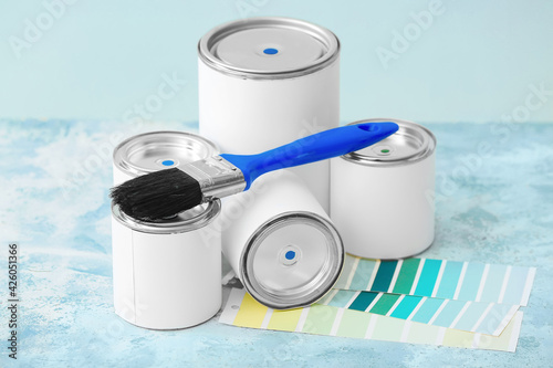Obraz Cans of paints, brush and palette samples on color background - fototapety do salonu