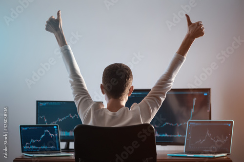 Billede på lærred successful male trader looking at monitor with stock exchange graph or chart