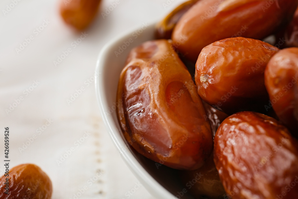 Fototapeta Bowl with sweet dried dates on light background, closeup