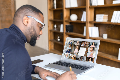 Webinars, online conference, video meeting. African-American businessman is using app on laptop for video connect with a many people at same time together, taking notes. Distant work concept