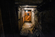 A Scary Dark Concrete Corridor In The Basement, Lit By A Single Light Bulb Hanging From The Low Ceiling. At The End Of The Corridor Is A Boarded-up Wooden Door