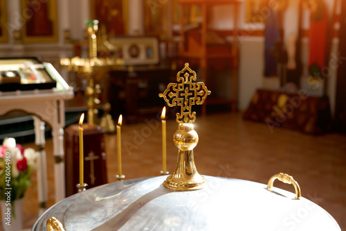 Fototapeta Orthodox cross in the sun on the lid of the bowl for the rite of infant baptism